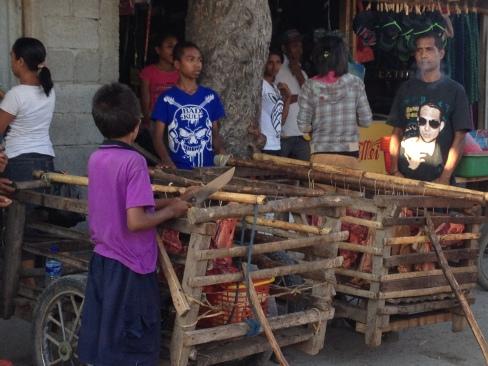 Meat Cart: Raw meat, probably pork, hangs inside a cart.