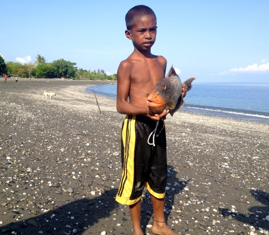 A boy shows us his catch of the day: A bumphead parrot fish.
